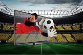 Composite image of fit goal keeper saving goal through tv against vast football stadium with fans in
