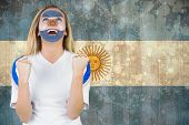 Excited argentina fan in face paint cheering against argentina flag in grunge effect