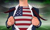 Businessman opening shirt to reveal usa flag against vast football stadium for world cup