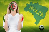 Excited iran fan in face paint cheering against football pitch with brazil outline and text