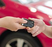 Female Hand Getting Modern Car Key On Red Car Background