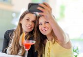 Smiling friends taking a self shot with phone