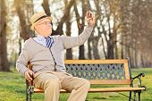 Elderly gentleman taking a selfie wit cell phone, seated on bench in park