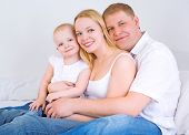 happy family: mother, father and baby in bed at home