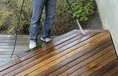 stock photo of pressure-wash  - Man using pressure washer to clean cedar deck - JPG
