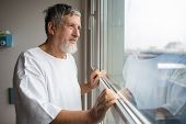 Patient at a hospital, looking from a window in his room, doing much better after the surgery