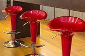 Interior of modern house, counter top with red stools, detail