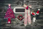 Wooden christmas background with red decoration and an empty sign or card for greetings. Ribbon german text: Merry christmas