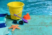 Summer time concept with toys, sunglasses, and starfish on painted wood