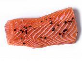 Delicious, raw salmon with peppercorn on a white background