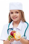 Little girl playing doctor - offering fresh fruits instead of medication, isolated