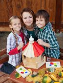 Woman and kids painting a new a bird house in autumn - preparing for winter