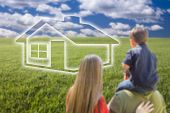 Young Family in Grass Field with Ghosted House In Front of Them.