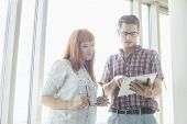 Creative businesspeople using digital tablet together in office