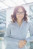Portrait of smiling businesswoman leaning on railing in office