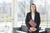 Portrait of businesswoman holding file while standing at office lobby