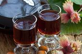 stock photo of hazelnut  - Homemade hazelnut liqueur in two glasses with hazelnuts on old wooden board - JPG