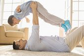 Side view of playful father lifting son while lying on floor at home