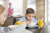 Siblings having breakfast at table with mother preparing food in background