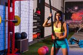 beautiful girl at gym with black rope and fit muscles