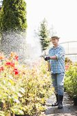 Full-length of man watering plants outside greenhouse