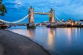 Tower Bridge And Thames River Lit By Moonlight At The Evening, London, United Kingdom