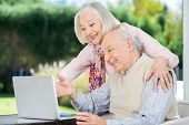 Cheerful senior couple using laptop at nursing home porch