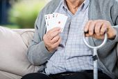 Midsection of elderly man showing four aces while sitting on couch at nursing home