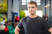 Portrait of confident young man standing at healthclub