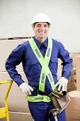 Portrait of a confident foreman in protective clothing standing in warehouse
