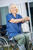 Smiling senior woman holding walking stick while sitting on wheelchair at nursing home yard