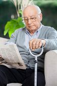 Elderly man reading newspaper while holding metal cane on couch at nursing home porch