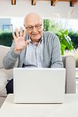 Cheerful senior man waving while video chatting on laptop at nursing home porch