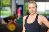 Portrait of confident fit woman smiling while standing in Gym