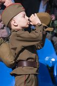 Young boy in World War 2 uniform drinks water