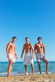 Three young muscular men jumping on the beach