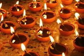 stock photo of pooja  - oil lamps illuminating in a row - JPG