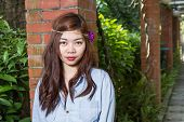 foto of filipina  - Pinoy woman in a green garden on farm leaning against brick pillar - JPG