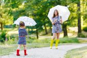 Happy Mother And Her Little Cute Kid Girl In Rain Boots