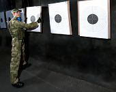 Man with target in shooting range in glases
