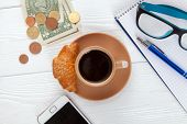 Coffee with croissant on a worktable