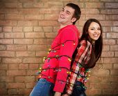 Happy Young Couple Near Brick Wall With Garland