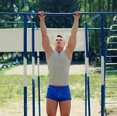 Workout, Sports Man Pulls On The Horizontal Bar