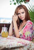 image of woman red blouse  - Attractive red hair young woman with bright colored blouse drinking lemonade on a terrace - JPG