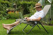 senior  in garden at leisure with laptop computer