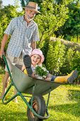 Grandfather giving granddaughter ride in wheelbarrow in the garden