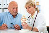 stock photo of spinal cord  - Physical therapist talking to patient and explains the cause of his pain - JPG