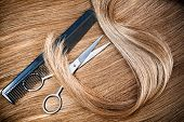 professional hairdresser scissors and comb on hair background