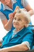 Caregiver dressing the hair of a senior woman. Home help