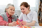 stock photo of hospice  - Elder care nurse playing jigsaw puzzle with senior woman in nursing home - JPG